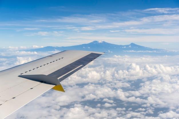 Blick aus dem flugzeugfenster des kilimanjaro-vulkans in den weißen wolken in tansania, ostafrika