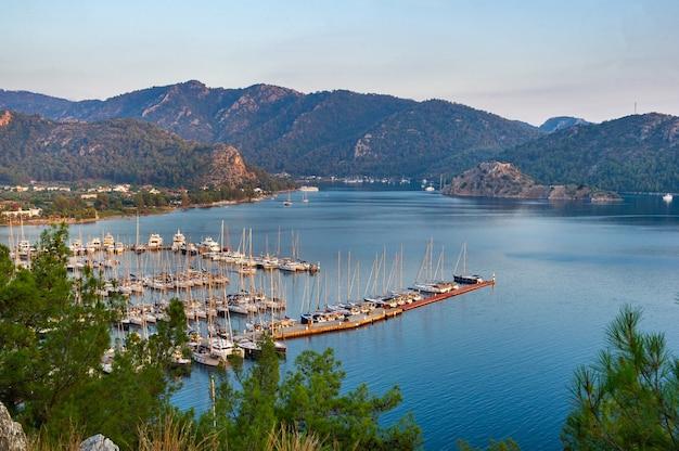 Blick aus der höhe auf die vielen luxusboote und yachten im yachthafen bei sonnenuntergang