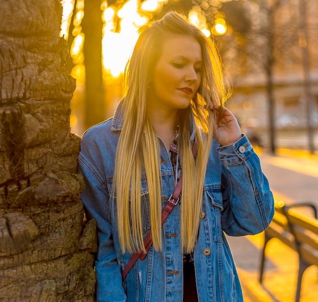 Blick der jungen blondine in einem baum mit einer jeansjacke auf einem sonnenuntergang