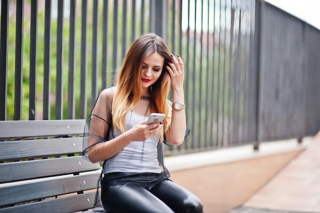 Blick der modernen frau auf weißes hemd, schwarze transparente kleidung, lederhosen, aufstellung an der straße und sitzen auf bank mit handy
