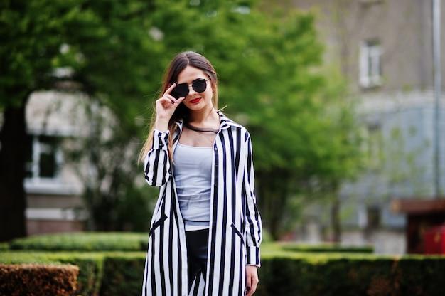 Blick der modernen frau mit der gestreiften schwarzweiss-anzugsjacke, lederhosen und sonnenbrille, die gegen büsche an der straße aufwerfen. konzept des modemädchens.