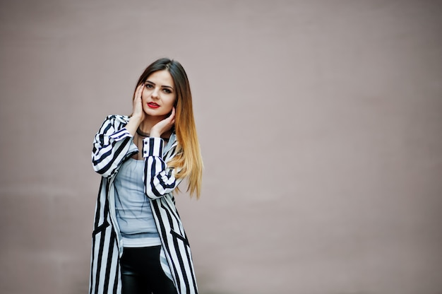 Blick der modernen frau mit gestreifter schwarzweiss-anzugsjacke, lederne hosen, die gegen wand aufwerfen. konzept des modemädchens.