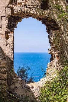 Blick durch altes verlassenes heruntergekommenes gebäude auf die blaue seelandschaft. adriatisches meer. apulien, italien.