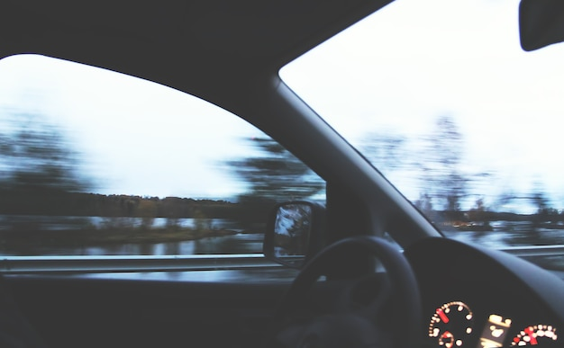 Blick durch die sich bewegende windschutzscheibe des autos in den innenraum.