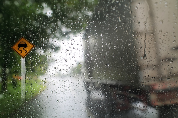 Blick durch die windschutzscheibe des regentages mit verkehrszeichen, flache schärfentiefe zusammensetzung.