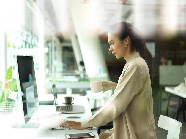 Blick durch glasfenster des weiblichen büroangestellten, der mit computer arbeitet und eine tasse getränk im büroraum hält