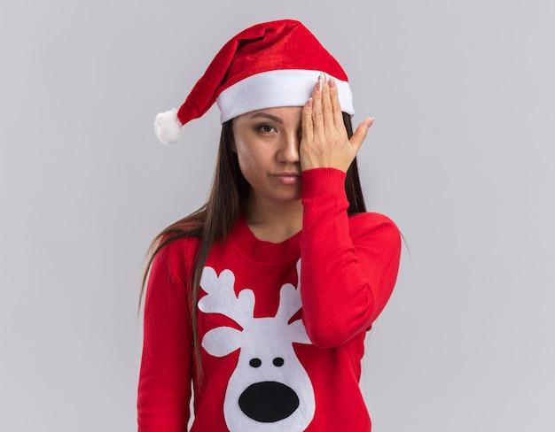 Blick in die kamera junges asiatisches mädchen mit weihnachtsmütze mit pullover bedecktes auge mit der hand isoliert auf weißem hintergrund