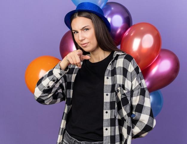 Blick in die kamera junges schönes mädchen mit partyhut, das vor ballons steht, zeigt auf die kamera