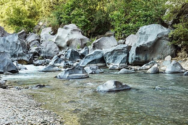 Blick mit mountain river und großen steinen auf dem boden. schlucht von alcantara auf der insel sizilien in italien. naturlandschaftsszene.