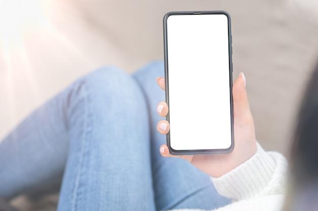 Blick über die schulter auf eine nicht erkennbare frau, die ein mobiltelefon mit leerem schwarzem bildschirm für das modell verwendet