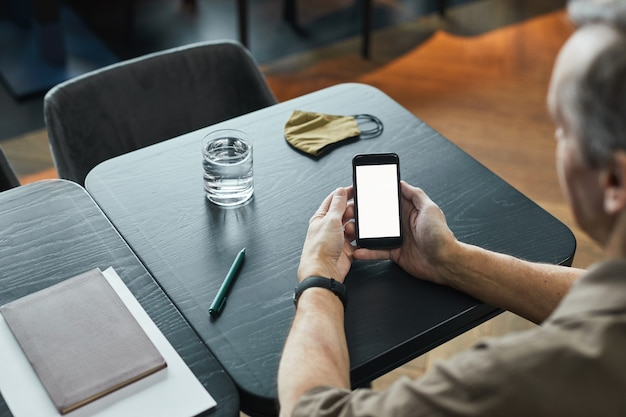Blick über die schulter auf einen alten mann, der mit einem glas wasser und einer stoffmaske am tisch sitzt und am telefon surft, leerer bildschirm