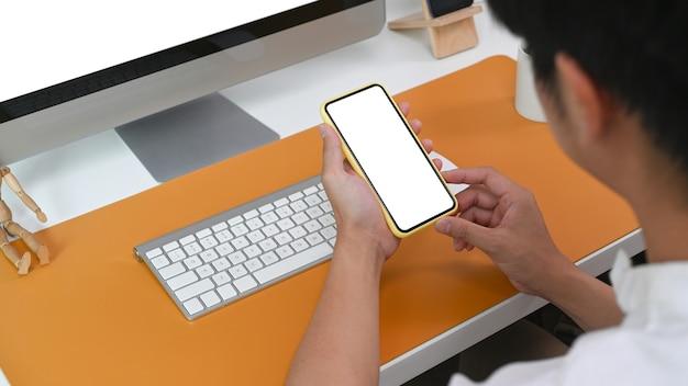 Blick über die schulter junger mann, der im büro sitzt und smartphone verwendet.