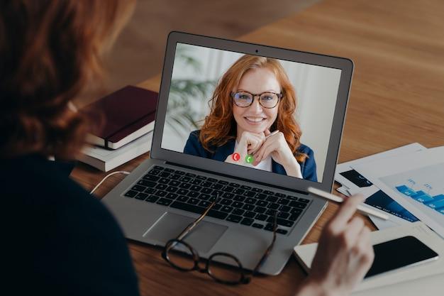 Blick über die schulter von weiblichen freiberuflern gespräche mit mitarbeiter per videoanruf, diskutieren strategie der arbeit. laptop-bildschirmansicht der lächelnden ingwerfrau in den brillen. einsatz neuer technologien. distanz arbeiten