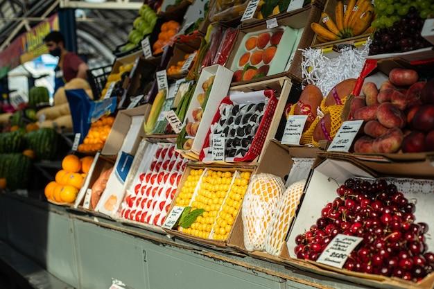 Blick über die theke voller frischer reifer früchte und beeren, bananen, mango, orangen, pfirsiche, sortiert in verschiedenen kartons zum verkauf. lokaler markt.