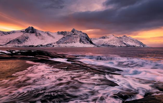 Blick über ersfjord von bunten felsen bei sonnenuntergang und felsenpools zu schneebedeckten bergen an einem dunklen bewölkten tag, kap tungeneset, senja, norwegen. europa. lange exposition