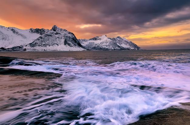 Blick über ersfjord von bunten felsen bei sonnenuntergang und felsenpools zu schneebedeckten bergen an einem dunklen bewölkten tag, kap tungeneset, senja, norwegen. europa. langzeitbelichtung