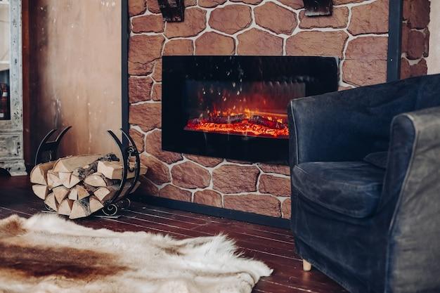 Blick über kamin mit brennenden baumstämmen, naturfellhaut auf dem boden neben halter mit baumstämmen in gemütlichem raum.