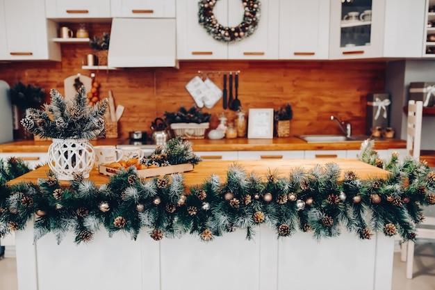 Blick über schöne weiße küche mit weihnachtsdekoration über schränke und küchenbrett. auf dem schrank steht weihnachtskranz. natürliche tannenzweige mit tannenzapfen.