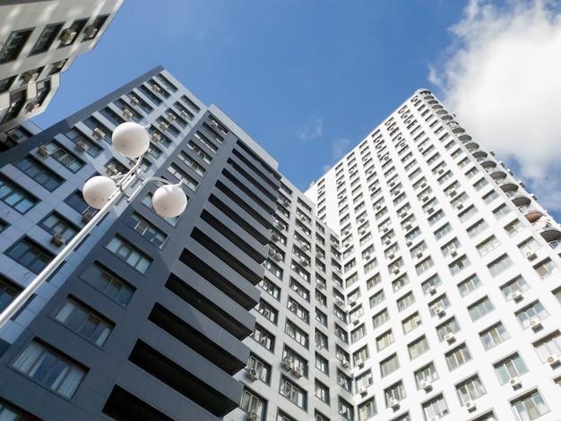 Blick vom boden auf die dächer des modernen mehrstöckigen wohngebäudes gegen blauen himmel und strahlende sonne