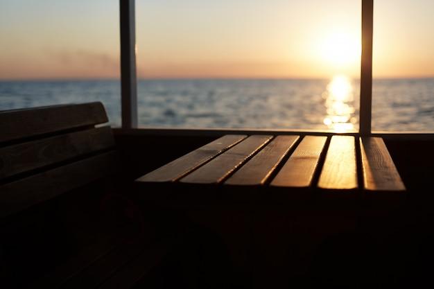 Blick vom deck auf den wunderschönen sonnenuntergang. nicht erkennbare person, die promenade auf kreuzfahrtschiff hat und schöne landschaften bewundert