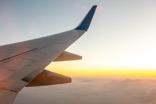 Blick vom flugzeug auf den weißen flügel des flugzeugs, der über wüstenlandschaft im sonnigen morgen fliegt.