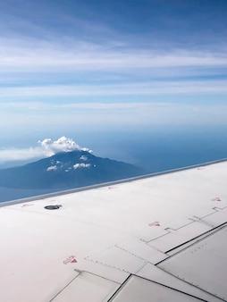Blick vom flugzeugfenster einer insel am sonnigen tag. flug- und reisekonzept