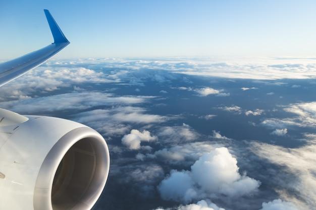 Blick vom flugzeugfenster und vom flügel mit himmel über flauschigen wolken. flug- und reisekonzept.