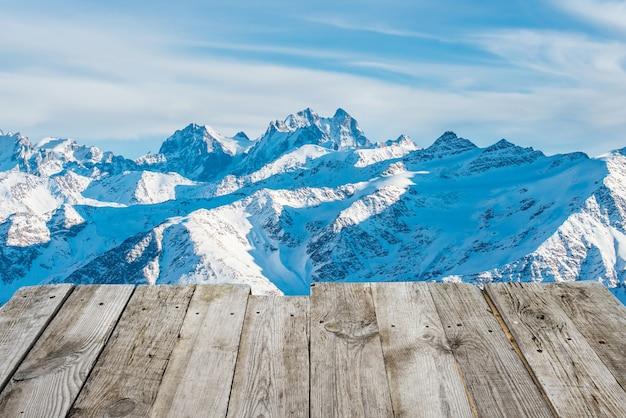 Blick vom leeren holzdeck auf die sonnigen winterberge im bokeh