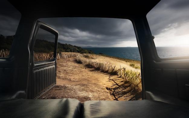 Blick vom offenen kofferraum auf berg und meer.