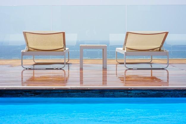 Blick vom pool auf die terrasse der hotelzimmer