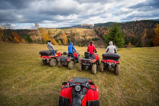 Blick vom quad mit vier männern auf dem atv vorne auf dem hügel