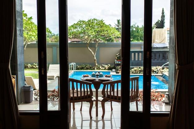 Blick vom zimmer, balinesisches tropisches frühstück mit obst, kaffee und omelett für zwei personen,