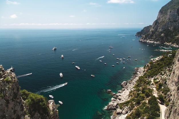 Blick von den gärten des augustus auf capri inselküste tyrrhenisches meer und segelboote italien