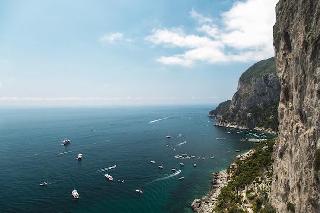Blick von den gärten des augustus auf der insel capri küste, meer und boote. italien.
