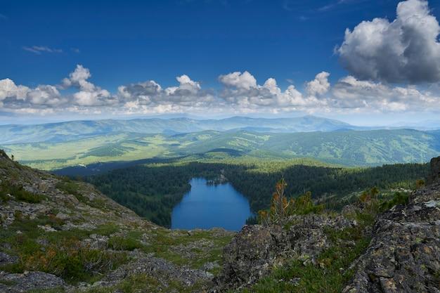 Blick von der bergspitze auf den blauen see, umgeben von nadelwald und gebirgszug. altai russland