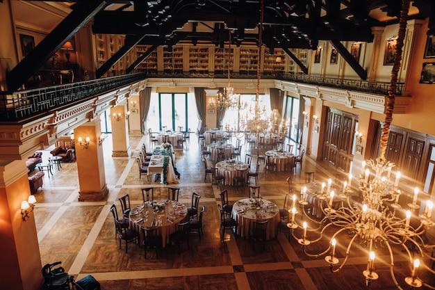 Blick von der decke des geschmückten festsaals mit runden tischen