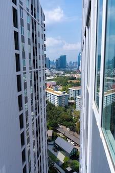 Blick von der oberen etage der straßen von bangkok. hohe gebäude und dächer kleiner häuser. stadtlandschaft