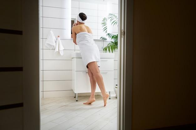 Blick von der rückseite einer frau, die vor einem spiegel in einem weißen badezimmer steht und sich selbst betrachtet