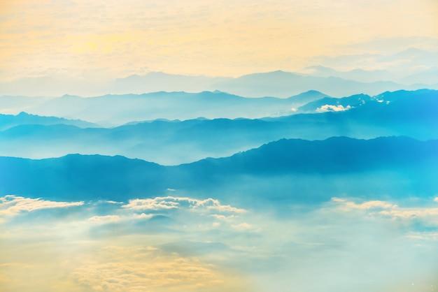 Blick von einem flugzeug auf den sonnenuntergang am himmel mit sonnenstrahlen. flauschiger wolkenhintergrund