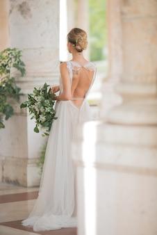Blick von hinten auf Braut mit Tattoos, die zwischen den Säulen stehen