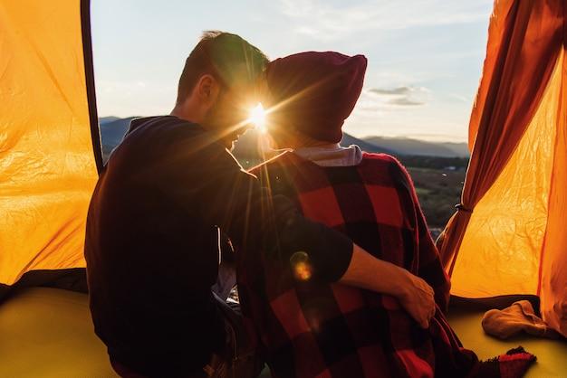 Blick von hinten auf den jungen mann und seine freundin, die in einem zelt sitzen