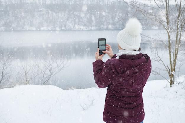 Blick von hinten auf eine frau in warmen kleidern, die ein smartphone hält und einen schuss schönen schnees macht