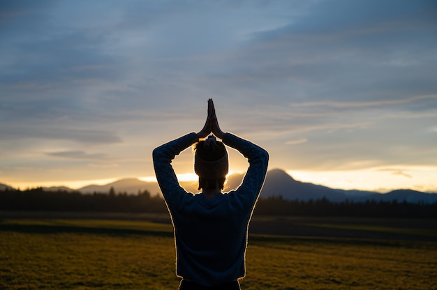 Blick von hinten auf eine junge frau, die mit ihren händen meditiert, verbunden über ihrem kopf draußen in der schönen natur bei sonnenuntergang, der im dramatischen himmel glüht.