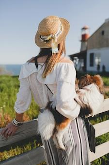 Blick von hinten auf eine stilvolle frau auf dem land, die einen hund hält