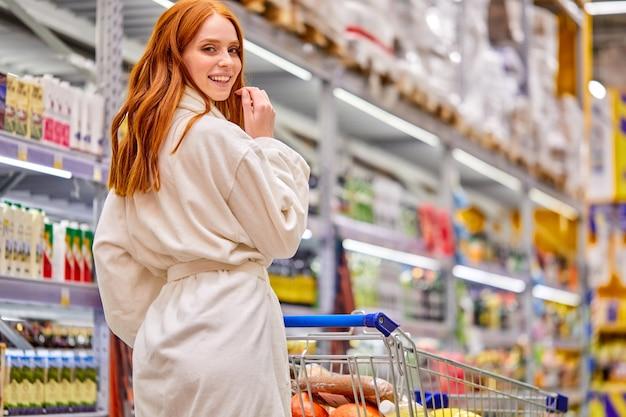 Blick von hinten auf frau im bademantel, die allein im supermarkt einkauft, zu fuß produkte wählt, mit wagen. im marktgang
