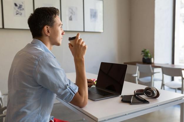 Blick von hinten auf gutaussehenden mann, der bei seiner arbeit beschäftigt ist, kaffee zu trinken