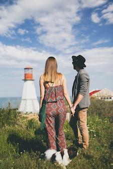Blick von hinten auf junges stilvolles hipster-paar in der liebe, das mit hund in der landschaft geht