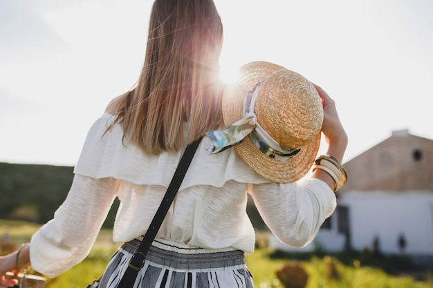 Blick von hinten auf sonnige schöne stilvolle frau, frühling sommer modetrend, boho-stil, strohhut, landschaftswochenende, lange haare