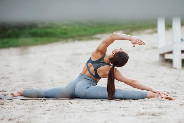 Blick von hinten. brünette mit schöner körperform in sportlicher kleidung haben fitness-tag am strand