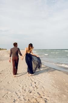 Blick von hinten. elegantes verliebtes paar, das entlang des strandes geht. romantische momente. weißer sand und meereswellen. tropischer urlaub. vollständige höhe.